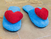 Blue shoes in house with red heart on floor at home — Stock Photo