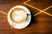 Cup of latte coffee on wood — Stock Photo