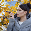 Young woman smokes on the background of autumn leaves — Stock Photo