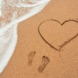 Shape of the heart and footprints in the sand on the beach — Stock Photo #36167165
