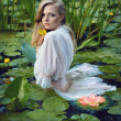 Stock Photo: Beautiful girl stands in middle of pond with lotuses
