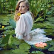 Beautiful girl stands in the middle of the pond with lotuses — Stock Photo #36170683