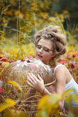 Beautiful fairy girl with golden cage in a forest — Stock Photo