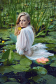 Beautiful girl stands in the middle of the pond with lotuses — Stock Photo