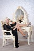 Pretty blonde woman in a luxury bedroom — Stock Photo