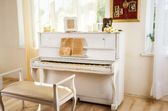 Old white piano in vintage interior — Stock Photo