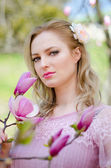 Beautiful blond girl among the spring flowering branches of magn — Stock Photo
