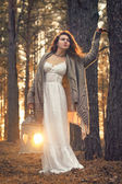 Young beautiful woman in the forest with lantern — Stock Photo