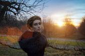 Beautiful young woman walking in the garden at sunset — Foto de Stock