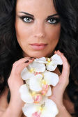 Beautiful dark haired girl with orchids on white background — Stock Photo