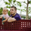 Father and daughter sitting on a bench — Stock Photo