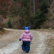 Little toddler girl walking in forest — Stockfoto