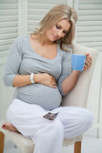 Attractive pregnant woman sitting at home on chair holding blue mug, smiling and touching her tummy — Stock Photo