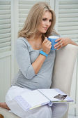 Attractive pregnant woman sitting at home on chair holding blue mug, contemplating, with baby scan and baby book on her lap — Stock Photo