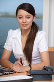 Beautiful young woman at work in office — Stock Photo