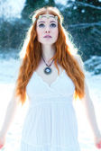 Snow Maiden. Whimsical image of beautiful red head woman standing in snow looking angelic — Stock Photo