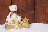 Teddy-bear sitting on present box — Stock Photo