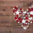 Christmas heart on a wooden background with different decoration — Stockfoto