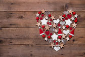 Christmas heart on a wooden background with different decoration — Zdjęcie stockowe