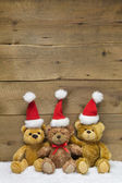 Three teddy bears with Christmas hats — Stock Photo