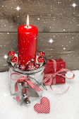 Red candle and gift box on snow — Stock Photo