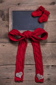 Chalkboard with knitted sock and bow — Stock Photo