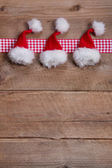 Wood background for christmas with santa hats — Stock Photo
