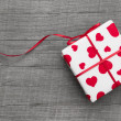 Gift box wrapped in heart patterned paper — Stock Photo