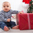 First Christmas: baby unwrapping a present — Stock Photo #33719579