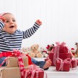 First Christmas: baby unwrapping a present — Стоковая фотография