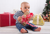 First Christmas: baby unwrapping a present — Stock Photo