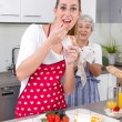 Young woman cooking and eating with her mother  in the kitchen - — Stock Photo