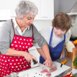 Grandmother teaching young boy to cook meat - family life at hom — Stockfoto