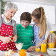 Happy family cooking together - with the grandmother — Stock Photo #34138233