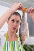 Frightened woman cooking fish in the kitchen — Stock Photo