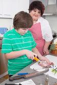 Mutter lehrt ihren sohn kochen fleisch - fett und übergewicht — Stockfoto