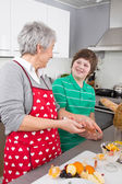 Grandmother teaching young boy to cook meat - family life at hom — Stock Photo