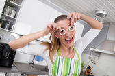 Young woman posing with onion rings in the kitchen — Stock Photo