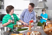 Father cooking with his children in the kitchen - family life — Stock Photo
