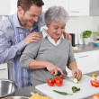 Man watching his mother cook at kitchen — Stock Photo #34140255