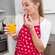 Young woman drinking orange juice in the kitchen — Stock Photo