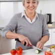 Senior woman cutting vegetables in kitchen — Stock Photo