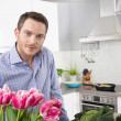 Happy man posing in the kitchen with pink tulips — Stock Photo