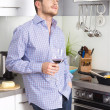 Happy well looking man drinking red wine in the kitchen — Stock Photo #34148615