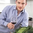 Happy well looking man drinking red wine in the kitchen — Stock Photo #34149115