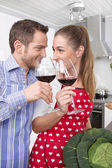 Loving couple drinking wine in the kitchen — Stock Photo