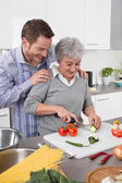 Man watching his mother cook at kitchen — Stock Photo