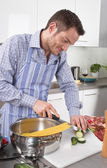 Happy man cooking pasta in the kitchen — Stock Photo