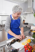 Senior woman preparing fish in kitchen — Stock Photo