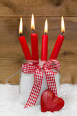 Christmas card: four red burning candles with ribbon and a red heart — Stock Photo